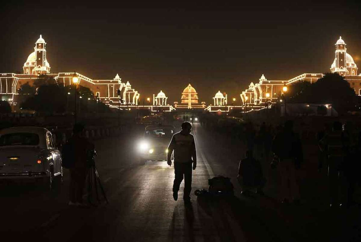 An Indian man walks on a road leading to an illuminated Raisina hill, which houses India's most important ministries and presidential palace, after the Beating Retreat ceremony, in New Delhi, India, Tuesday, Jan. 29, 2013. The ceremony is held annually on Jan. 29, which marks the end of republic day celebrations. (AP Photo/Manish Swarup)