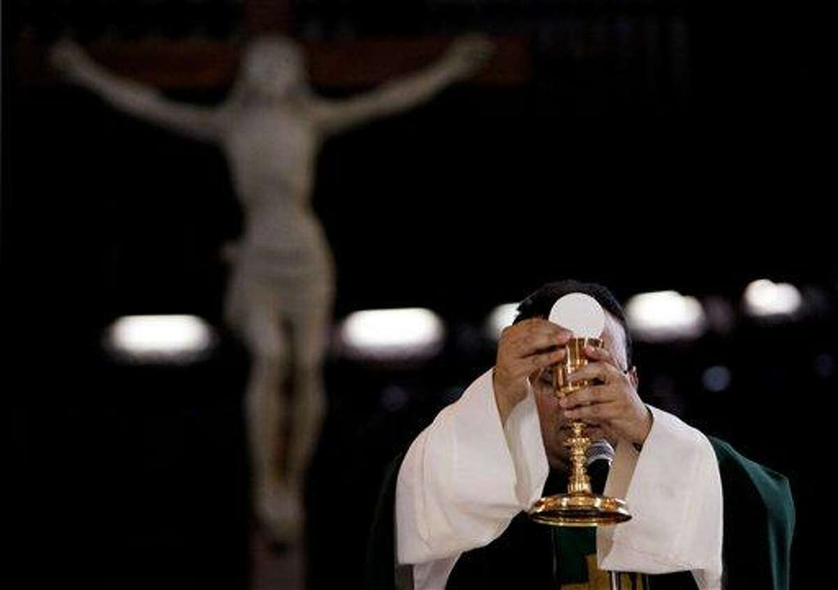 In this May 29, 2013 photo, a priest blesses the wine and bread as he celebrates Mass at a Catholic church in Caracas, Venezuela. Church officials say food shortages and foreign exchange restrictions are causing a lack of ingredients needed to celebrate Mass: altar wine as well as wheat to produce communion wafers. Venezuela has maintained strict currency controls since 2003, creating a black market that now sells dollars at more than triple the official rate of 6.3 bolivars. Falling oil exports and foreign investment have helped dry up the dollar supply. (AP Photo/Fernando Llano)