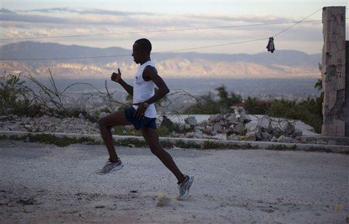 FILE - In this Jan. 7, 2013 file photo, Astrel Clovis, a 42-year-old marathon runner, trains in the early morning in Petionville, a suburb of Port-au-Prince, Haiti. Six days a week, Clovis sets off at daybreak and has been running the hills and streets of Port-au-Prince for the past 10 years. He decided to take the sport seriously after he entered a race in downtown Port-au-Prince on a whim - and won. Clovis' story inspired the J/P Haitian Relief Organization to sponsor five Haitian runners so they can compete in the New York City Marathon in November 2013. Sean Penn's relief organization will accept the top three men and two women finishers in a rare half-marathon that will wind through the Haitian capital of Port-au-Prince on Sunday, June 1, 2013.