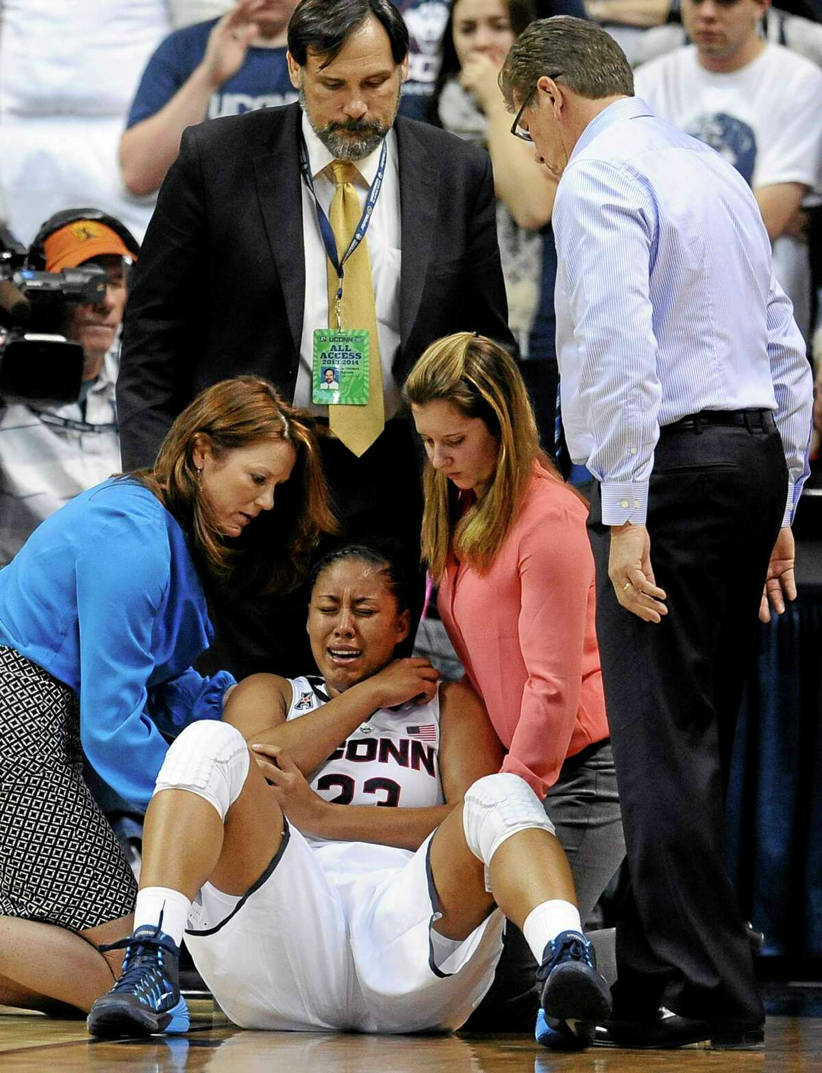 Connecticut head coach Geno Auriemma, right, looks at injured player Kaleena Mosqueda-Lewis, center, as she is tended to by assistant athletic trainer Rosemary Ragle, left, Team Physician Dr. Thomas Trojian, top center, and student athletic trainer Lauren Sheldon, second from right, during the second half of an NCAA college basketball game, Monday, Nov. 11, 2013, in Storrs, Conn. Mosqueda-Lewis left the game with an injury to her right elbow. Connecticut won 76-57. (AP Photo/Jessica Hill)