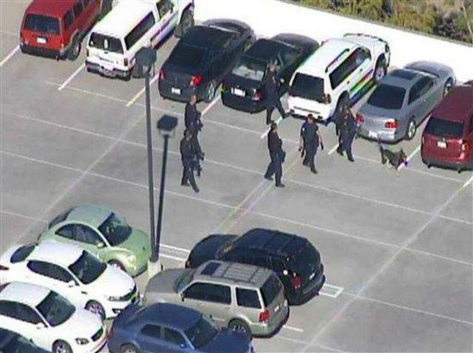 """This frame grab provided by <a href=""""http://abc15.com"""">abc15.com</a> shows the scene at a Phoenix office complex where police say a gunman shot at least three people on Wednesday, Jan. 30, 2013. Officer James Holmes said the victims were taken to hospitals and did not know if their injuries were life threatening. (AP Photo/abc15.com) Photo: AP / Abc15.com"""