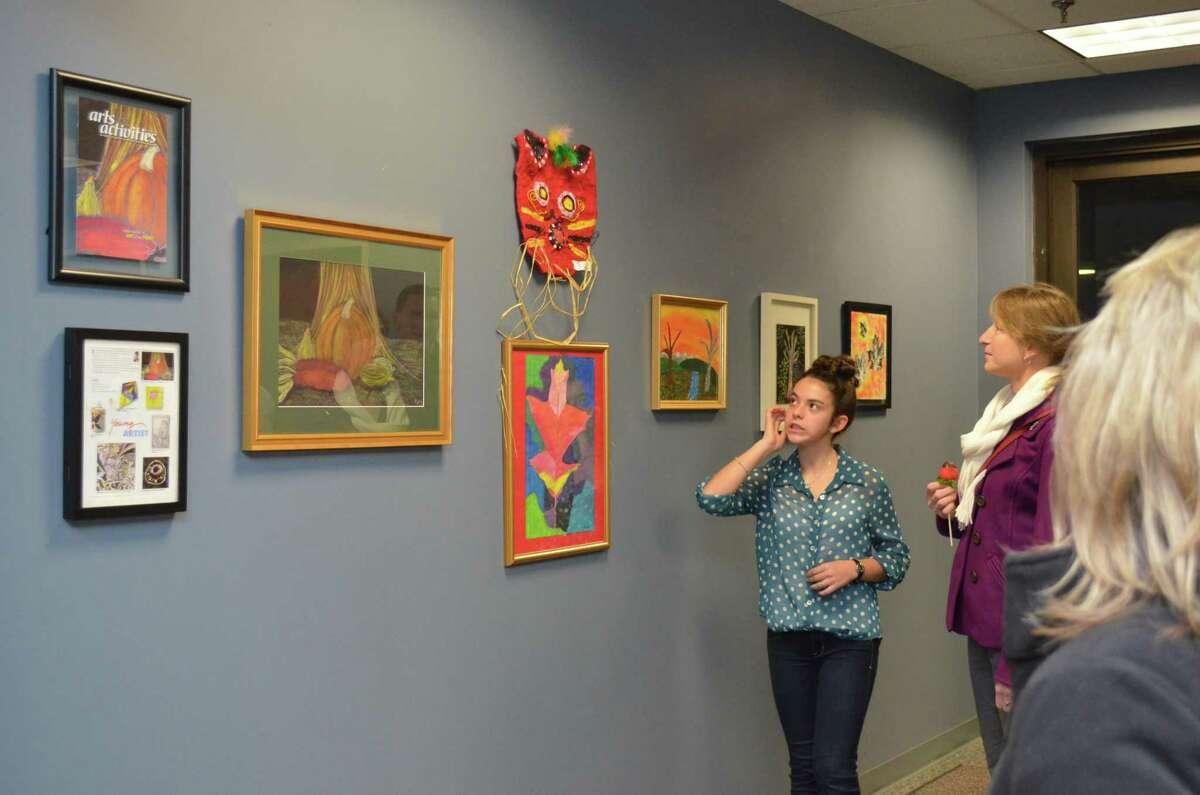 Decemeber's Artist of the Month, Aime' Freedenberg walks people through her art at her artist reception.
