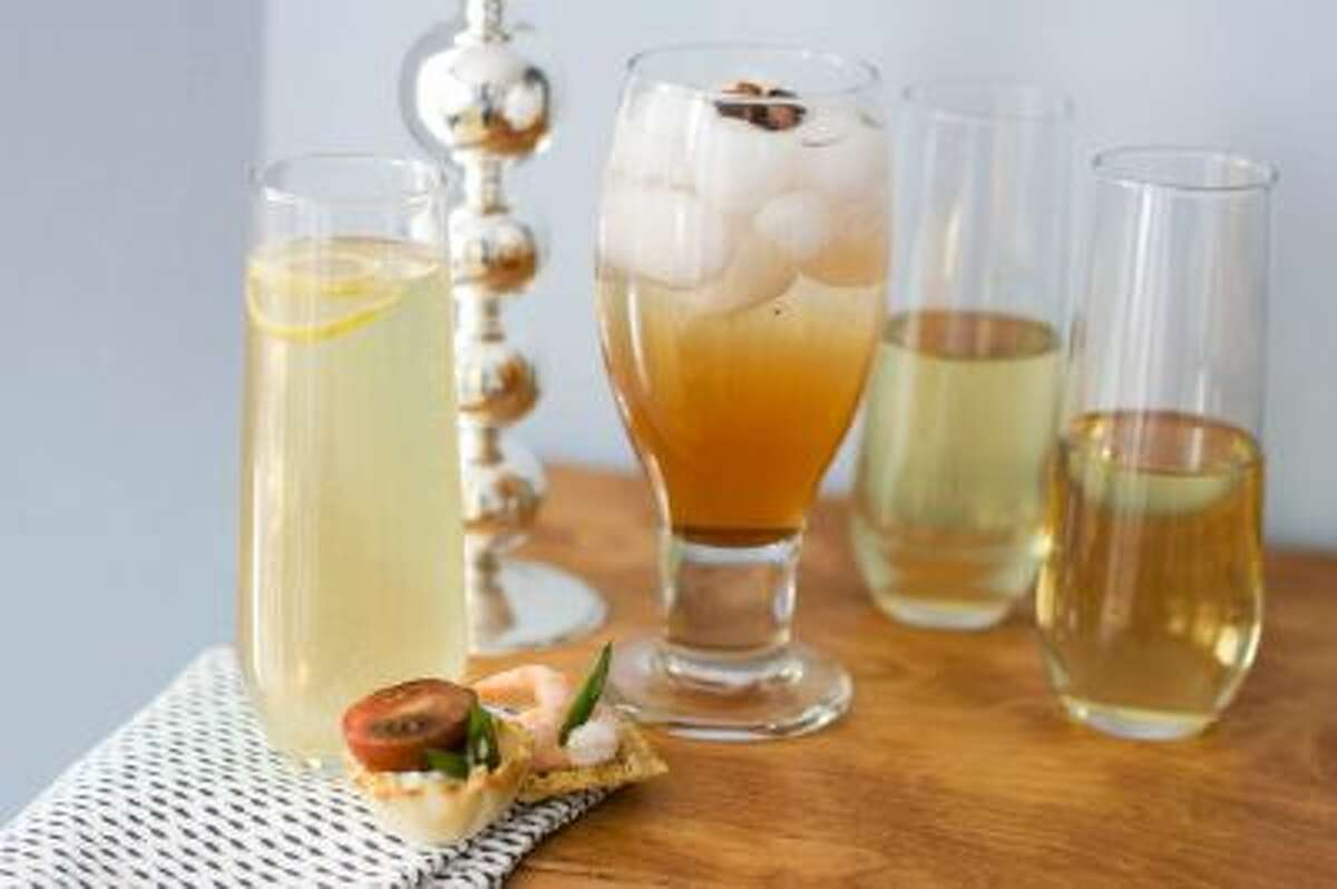 From left, a glass of citrus bubbly with a small curl of lemon on top, a glass of spiced rose-pomegranate spritzer with a star anise on top, and two glasses of sparkling wine, with canapes are shown.