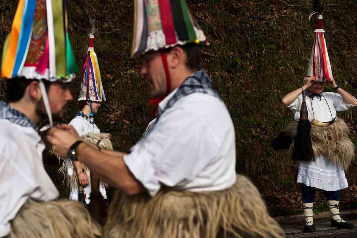 Joaldunak take part on the Carnival of the Basque village of Zubieta, Monday, Jan. 28, 2013. Every January, villagers from Zubieta parade to the neighbouring town of Ituren for Carnival, symbolizing the triumph of good over evil and involving the participation of residents wearing different masks, animal skins and brightly colored clothing with its own complex function and symbolism and becoming the living example of the survival of archaic cults to nature(AP Photo/Daniel Ochoa de Olza)