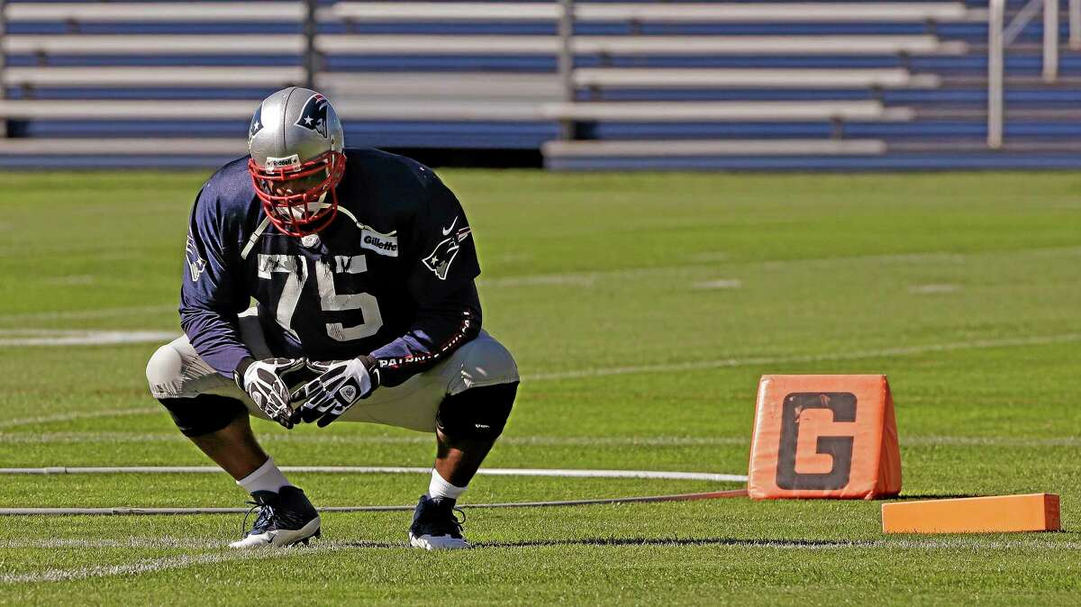 Patriots defensive tackle Vince Wilfork squats during a stretching and drills session before a practice earlier this season.