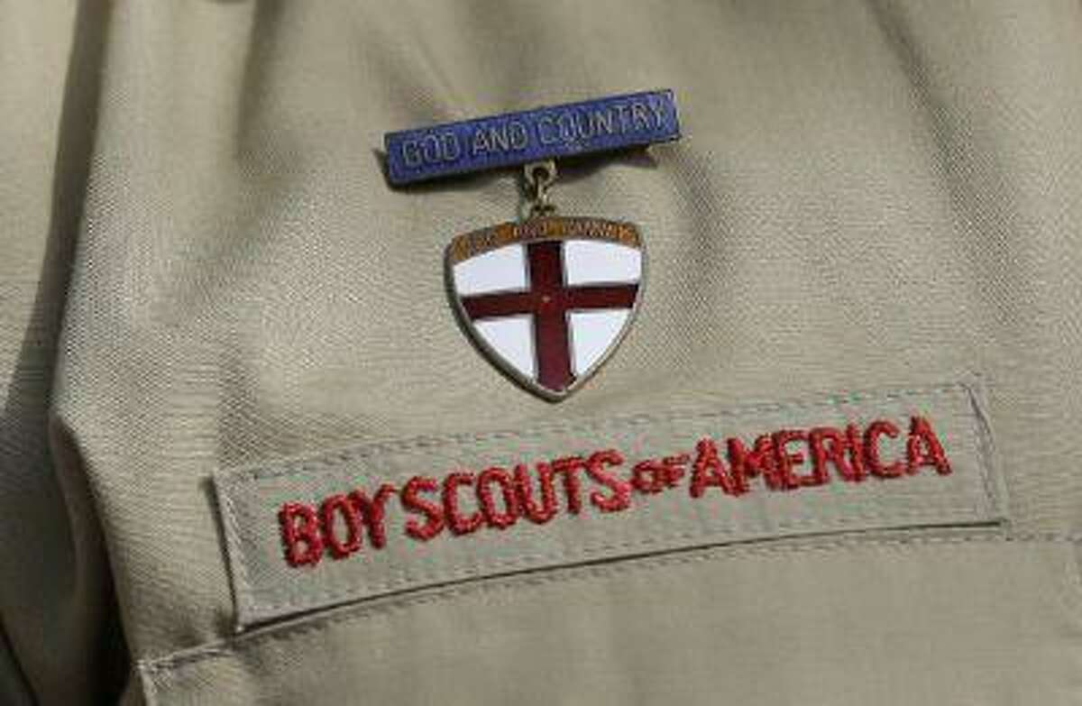 This photo taken Monday, Feb. 4, 2013, shows a close up detail of a Boy Scout uniform worn by Brad Hankins, a campaign director for Scouts for Equality, as he responds questions during a news conference in front of the Boy Scouts of America headquarters in Irving, Texas. (Tony Gutierrez/The Associated Press)
