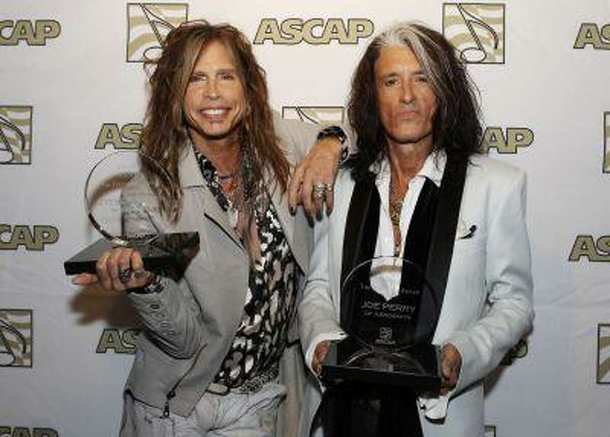 Steven Tyler (L) and Joe Perry of the group Aerosmith pose with the ASCAP Founders Award during a photo opportunity in Los Angeles April 8, 2013.
