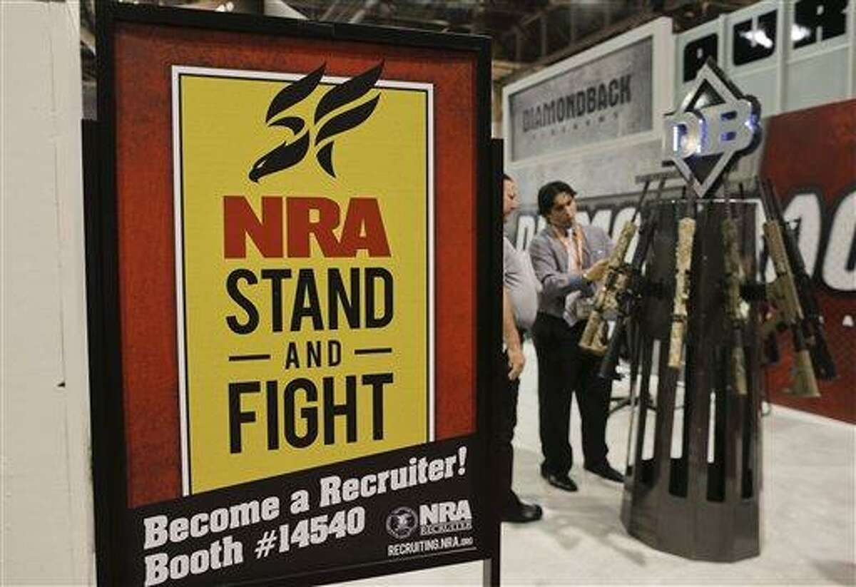 A Diamondback Firearms representative, rear right, explains features of one of their rifles on display at the 35th annual SHOT Show, Wednesday, Jan. 16, 2013, in Las Vegas. President Barack Obama urged a reluctant Congress on Wednesday to require background checks for all gun sales and ban both military-style assault weapons and high-capacity ammunition magazines in an emotion-laden plea to curb gun violence in America. His proposals, most of which are opposed by the powerful National Rifle Association and its allies in Washington, face a doubtful future in a divided Congress where Republicans control the House of Representatives. (AP Photo/Julie Jacobson)