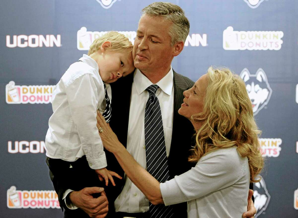 UConn interim head coach and former offensive coordinator T.J. Weist, center, holds his son James, left, as his wife Karen, right, watches, after a news conference Monday.