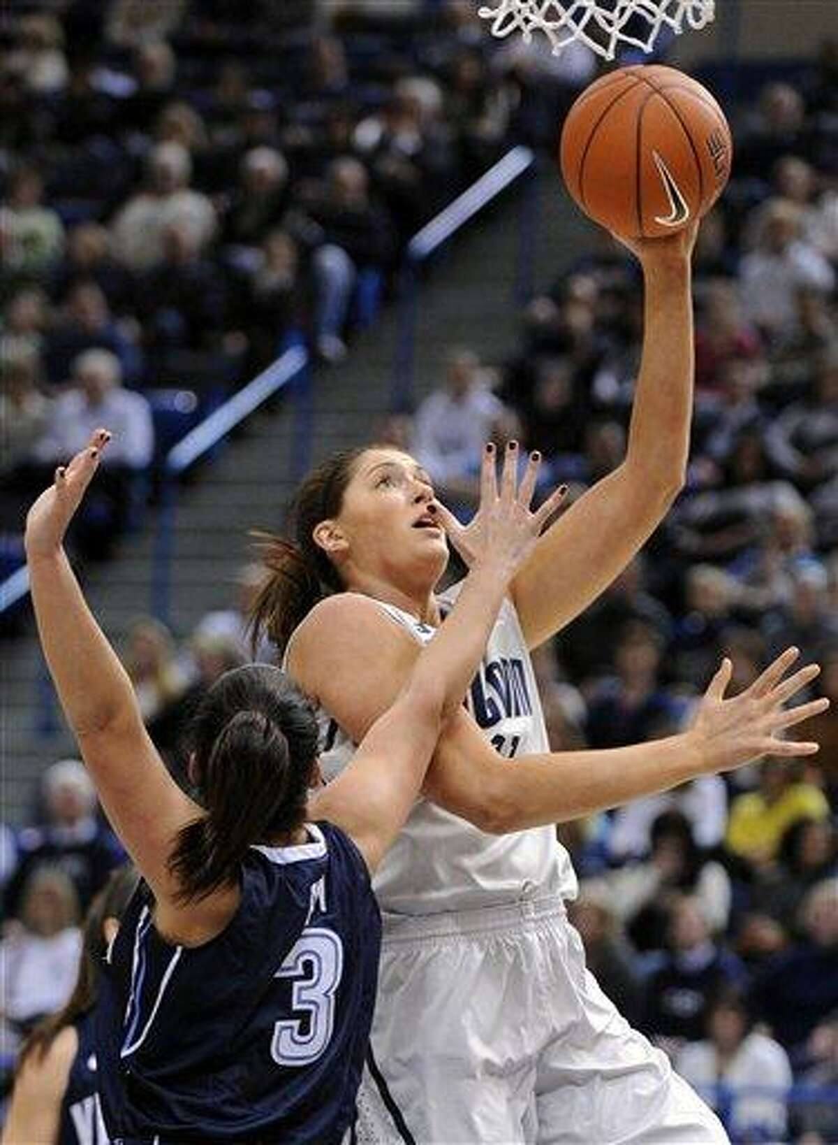 Connecticut's Stefanie Dolson, right, scores while being guarded by Villanova's Jesse Carey during the first half of an NCAA college basketball game in Hartford, Conn., Tuesday, Jan. 29, 2013. (AP Photo/Fred Beckham)