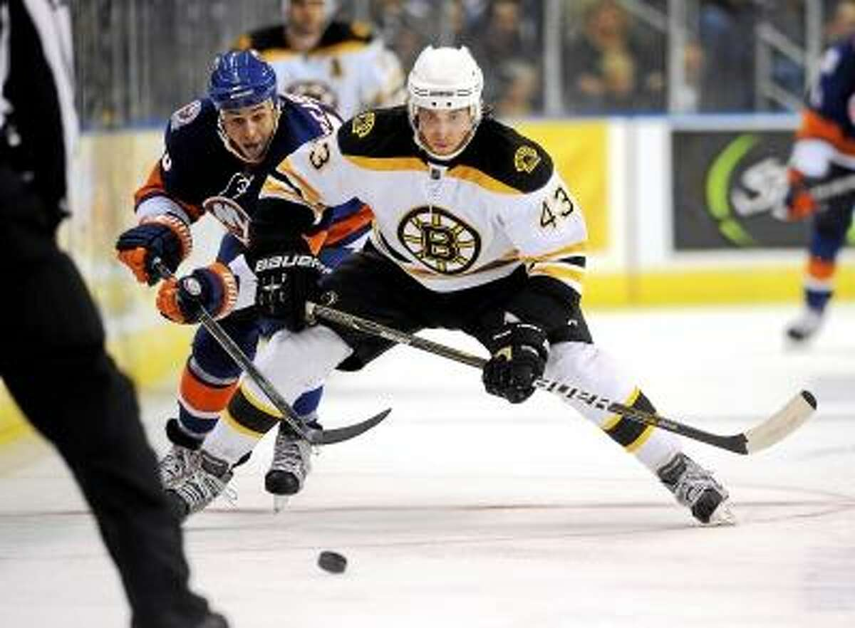 Boston Bruins' Matt Bartkowski fights for a puck with New York Islanders' Marty Reasoner during the third period of a preseason game. Photo by Fred Beckham/AP