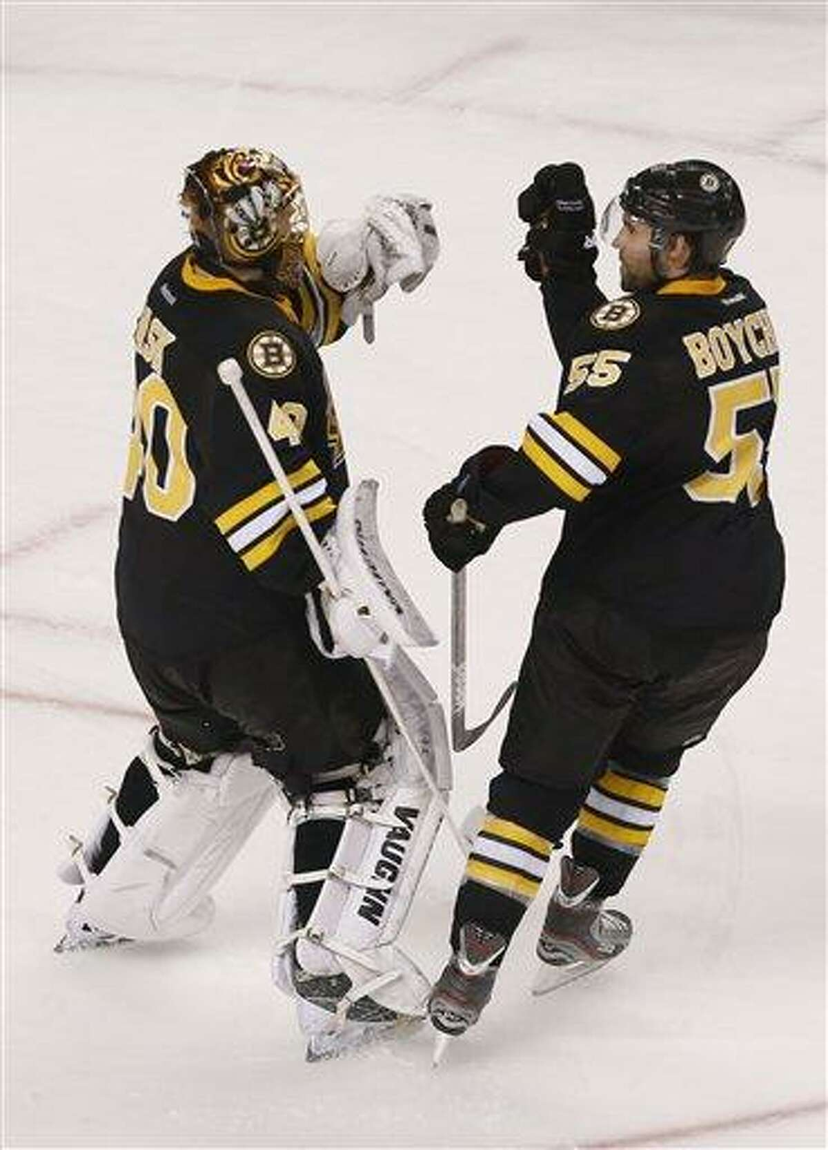 Boston Bruins goalie Tuukka Rask (40) is congratulated by teammate Boston Bruins defenseman Johnny Boychuk (55) after a win during a shoot out of an NHL hockey game in Boston, Tuesday, Jan. 29, 2013. (AP Photo/Charles Krupa)