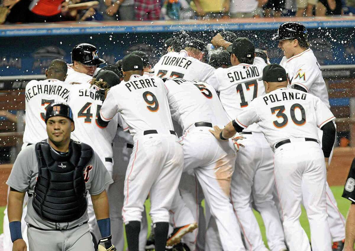 Miami Marlins mob pitcher Henderson Alvarez as Tigers catcher Brayan Pena, left, walks away after Alvarez threw a ho-hitter in a 1-0 win in Miami on Sunday.