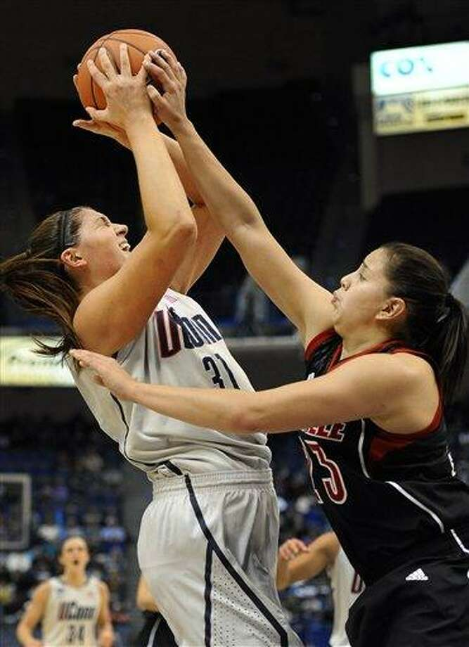 Connecticut's Stefanie Dolson, left, is pressured by Louisville's Shoni Schimmel, during the first half of an NCAA college basketball game in Hartford, Conn., Tuesday, Jan. 15, 2013. (AP Photo/Jessica Hill) Photo: ASSOCIATED PRESS / A2013