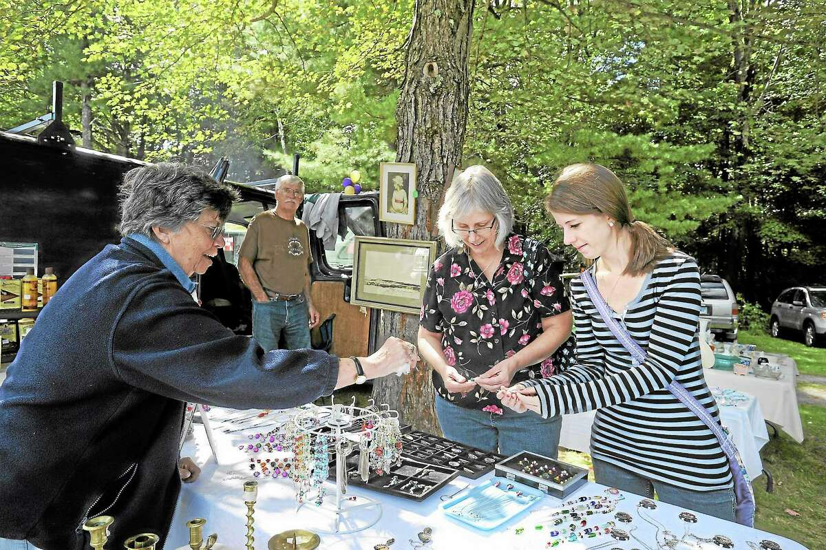 Marilyn Shorette shows jewelry and other things to Carol Anderson and Carolyn Anderson at the flea market at Brodie Park organized by the Lions' Club in New Hartford.
