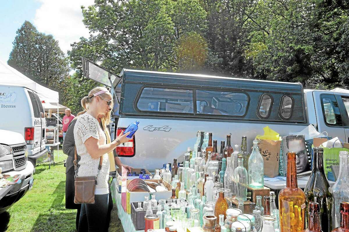 Sara Messick looks at one of the collection of bottles available for sale from one of the 100+ vendors at the flea market at Brodie Park organized by the Lions' Club in New Hartford.