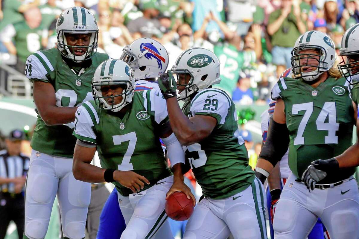 New York Jets quarterback Geno Smith (7) celebrates with teammates Bilal Powell (29) and Stephen Hill (84) after scoring a touchdown during Sunday's game against the Buffalo Bills in East Rutherford, N.J.