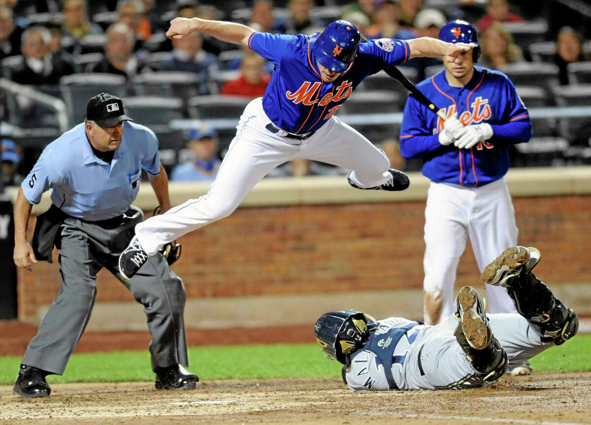 The Mets' Daniel Murphy jumps over Milwaukee Brewers catcher Martin Maldonado attempting to score as umpire Dale Scott, left, and batter Travis d'Arnaud, right, look on during the sixth inning of Friday's game in New York. Murphy was tagged out after he didn't touch the plate.