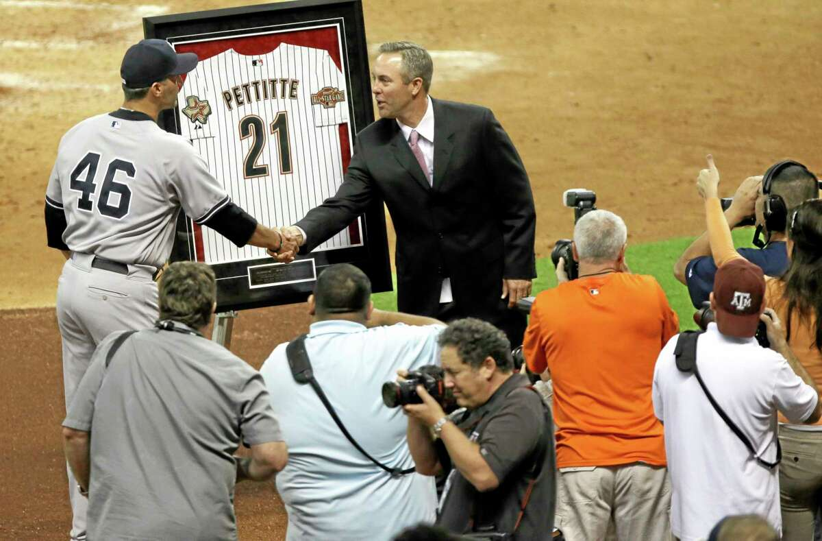 Yankees pitcher Andy Pettitte (46) shakes hands with Houston Astros president Reid Ryan as he is presented with a framed Astros jersey in the fifth inning of a baseball game on Friday, Sept. 27, 2013, in Houston. Pettitte, who is retiring at the end of this season, played for the Astros during their World Series season.