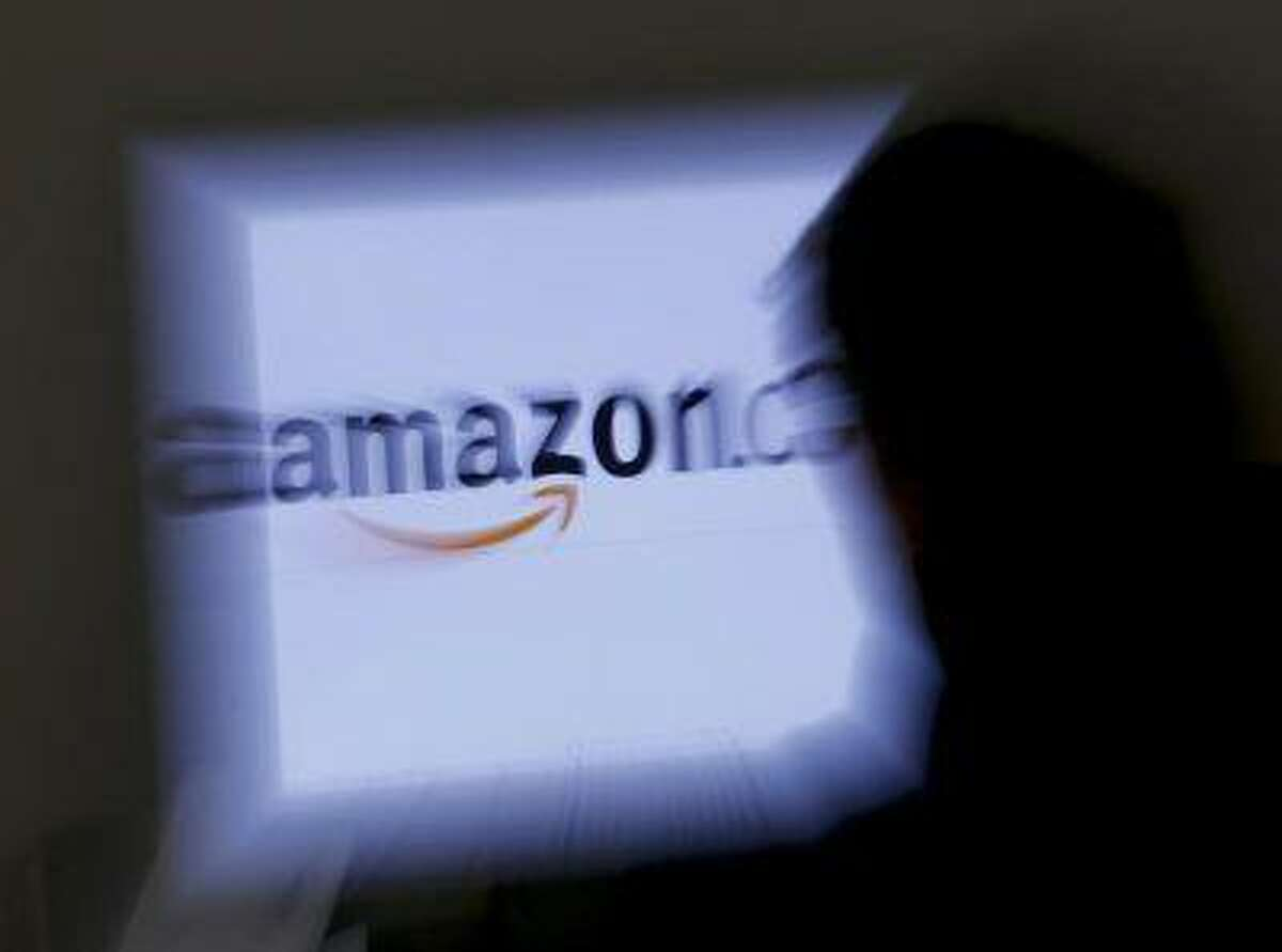 A zoomed illustration image of a man looking at a computer monitor showing the logo of Amazon is seen in Vienna November 26, 2012.