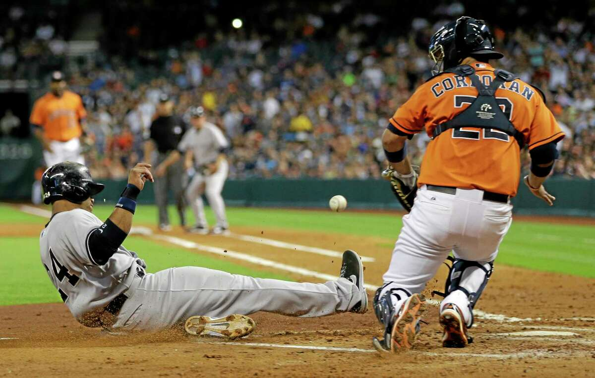 The Yankees' Robinson Cano, left, slides safely across home plate to score as Astros catcher Carlos Corporan waits for the ball during the fourth inning of New York's 3-2 win Friday night in Houston.
