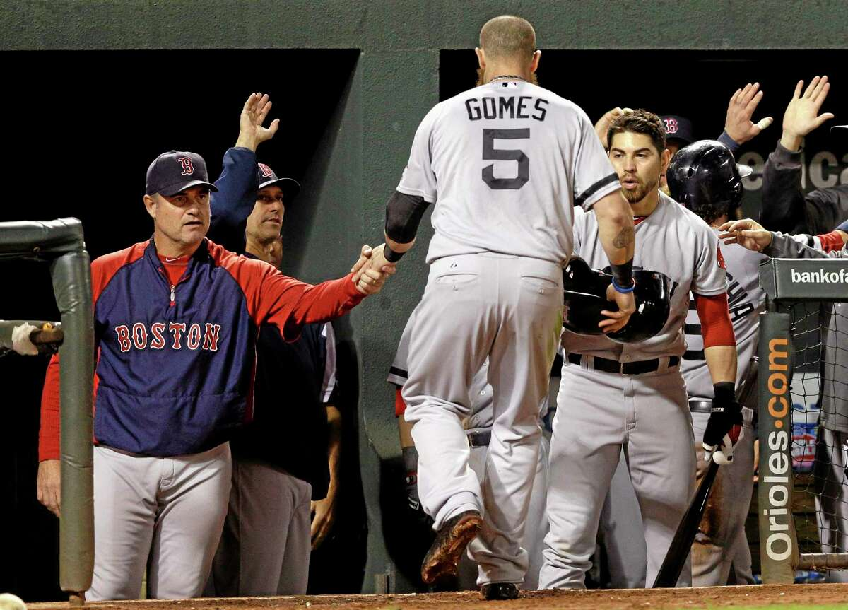 Boston Red Sox manager John Farrell, left, greets Jonny Gomes in the dugout after Gomes and Jarrod Saltalamacchia scored on a single by Stephen Drew in the third inning of Friday's game in Baltimore.