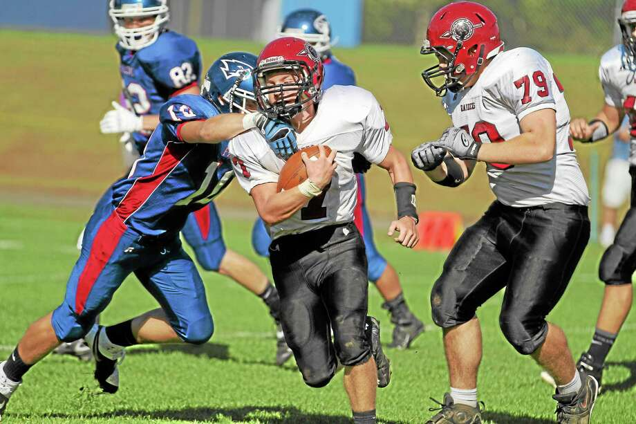 Torrington's Tyler Marens rushes during the Red Raiders 52-37 loss to St. Paul. Photo: Marianne Killackey — Special To The Register Citizen  / 2013