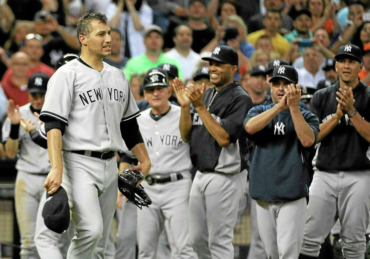 New York Yankees teammates applaud for starting pitcher Andy Pettitte, left, after earning the win over the Houston Astros 2-1 for his final Major League baseball game Saturday.