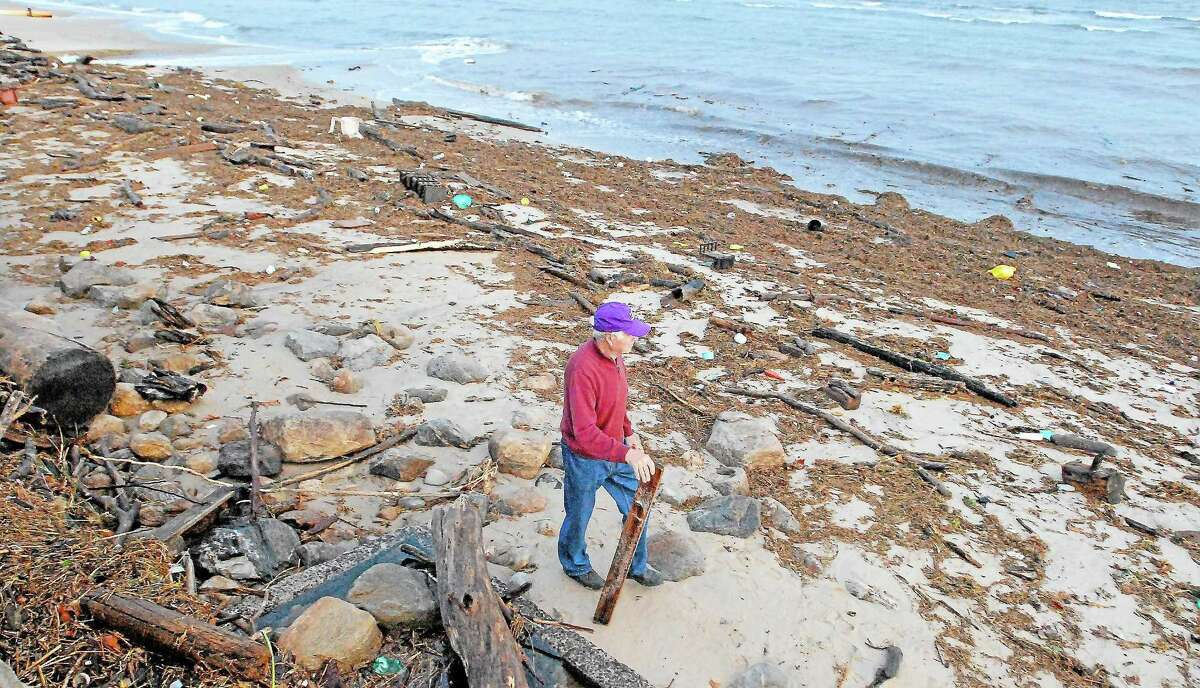Catherine Avalone/The Middletown Press ¬ Westbrook resident Nick DeMarco walks along West Beach which is covered by debris left by Hurricane Sandy.