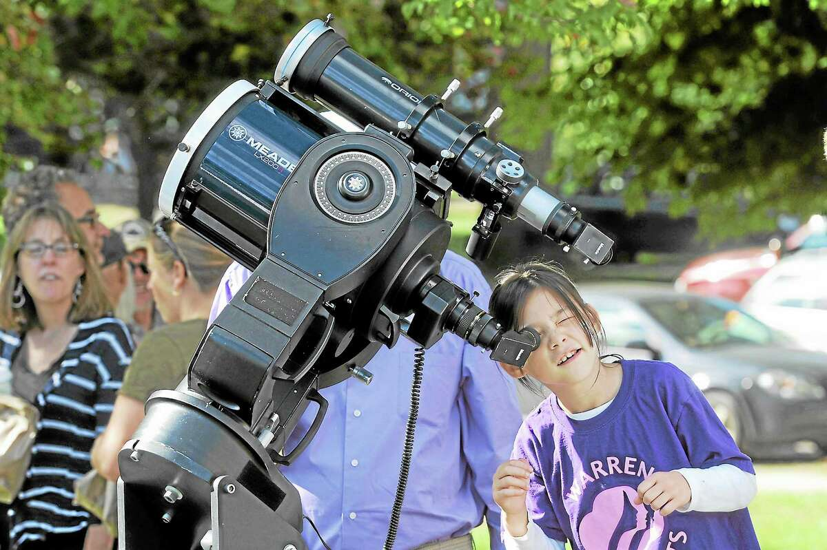 Ava Churyk, 8, checks out a telescope to observe sun spots at the 32nd annual Family Nature Day at White Memorial Conservation Center in Litchfield.Laurie Gabaordi - Register Citizen