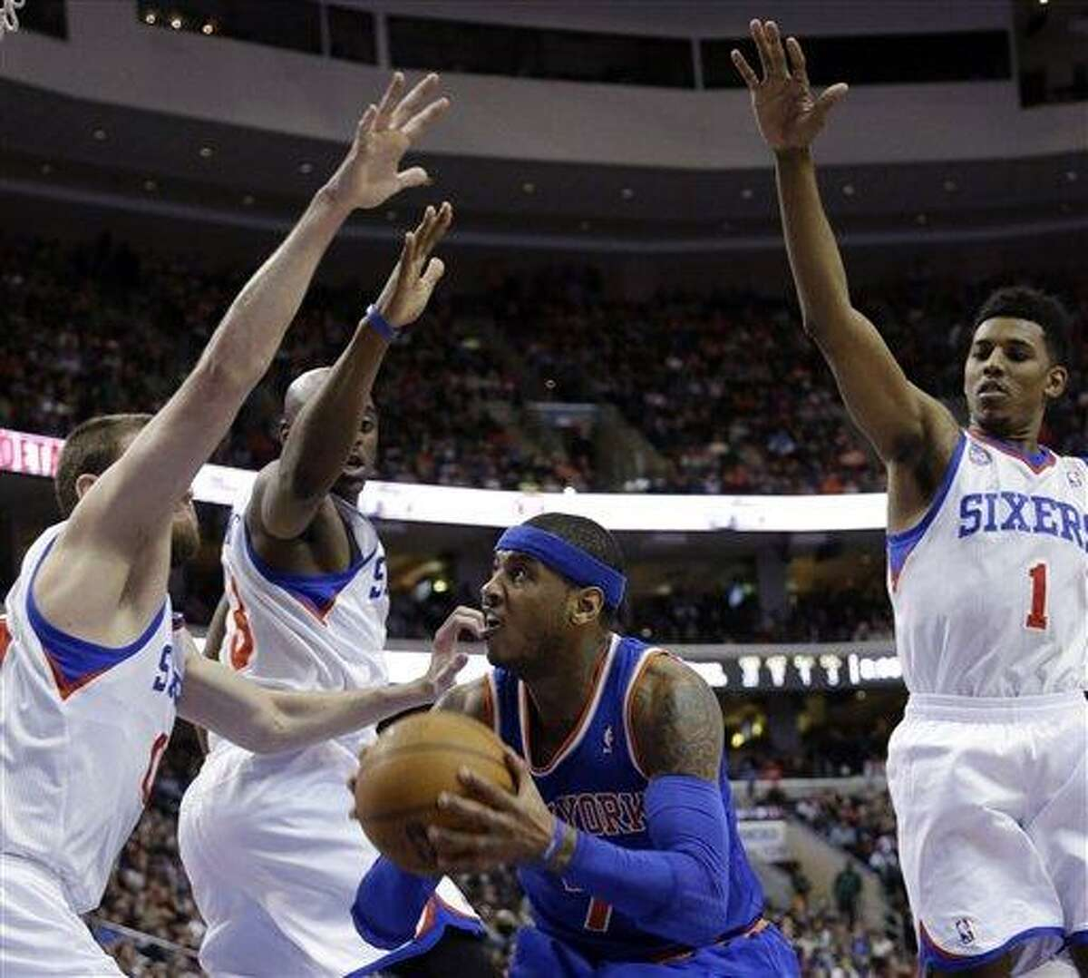New York Knicks' Carmelo Anthony, center, tries to go up for a shot as, from left to right, Philadelphia 76ers' Spencer Hawes, Damien Wilkins and Nick Young defend during the first half of an NBA basketball game on Saturday, Jan. 26, 2013, in Philadelphia. (AP Photo/Matt Slocum)
