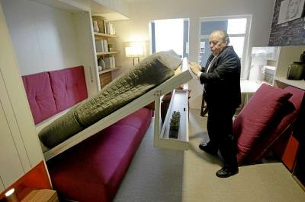 AP Photo/Seth Wenig Jack Sproule tries out a fold-down bed in a 325 square foot model apartment at an exhibit called