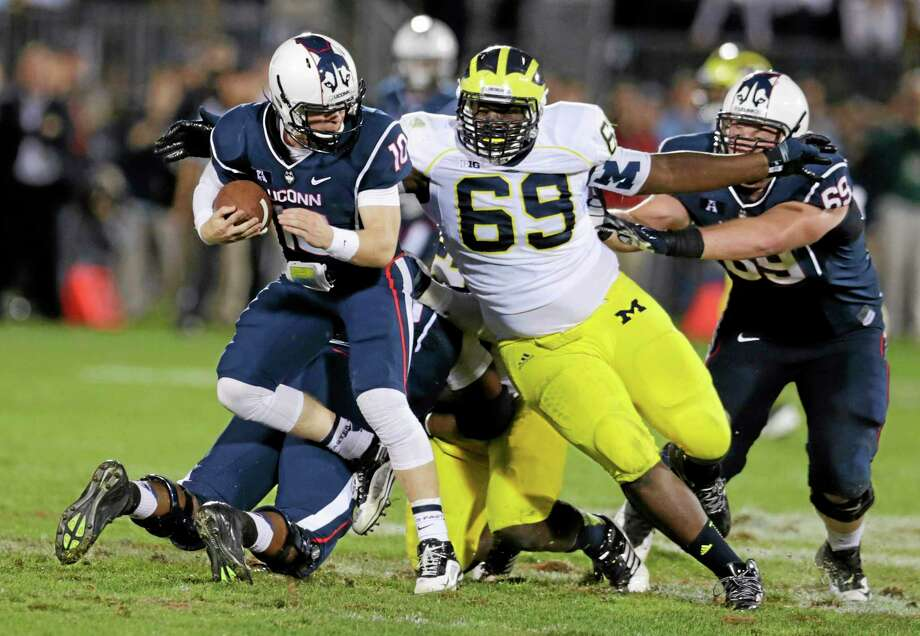 Michigan defensive tackle Willie Henry (69) chases down UConn quarterback Chandler Whitmer during the Wolverines' 24-21 win Saturday at Rentschler Field in East Hartford. Photo: Charles Krupa — The Associated Press  / AP