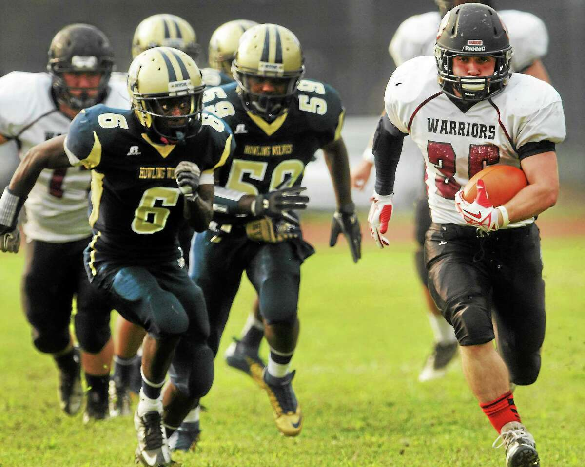 (Photo by Peter Hvizdak — Register)Justin Cheverier of Valley Regional runs for touchdown during firsts quarter football action against William Gardner, left, and Jaquaine Manley, center, of Hyde Leadership Academy at Wilbur Cross H.S. Thursday, September 12, 2013