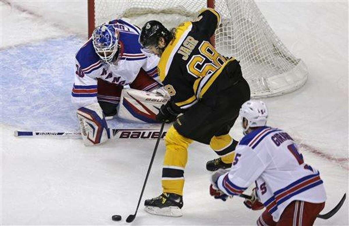 Boston Bruins right wing Jaromir Jagr (68) skates past New York Rangers defenseman Dan Girardi (5) as he sets to shoot against Rangers goalie Henrik Lundqvist (30) during the first period in Game 1 of an NHL hockey playoffs Eastern Conference semifinal game in Boston, Thursday, May 16, 2013. (AP Photo/Charles Krupa)