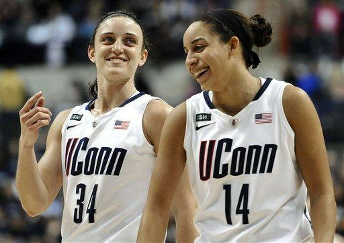 Connecticut's Kelly Faris (34) and Connecticut's Bria Hartley (14) smile during the second half of an NCAA college basketball game against Duke in Storrs, Conn., Monday, Jan. 21, 2013. Connecticut won 79-49. (AP Photo/Jessica Hill)