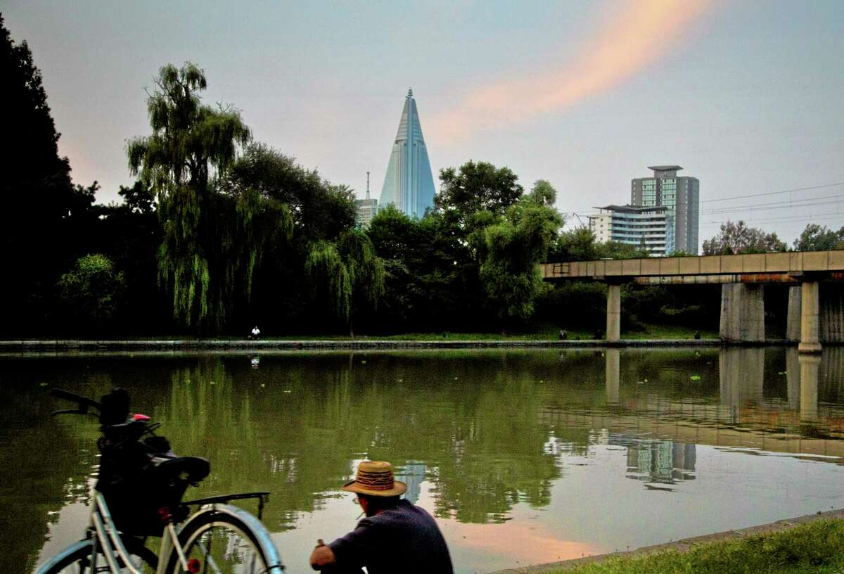 A North Korean man sits along a river as the sun sets over the unfinished 105-story Ryugyong Hotel in Pyongyang Wednesday, Sept. 18, 2013. (AP Photo/David Guttenfelder)