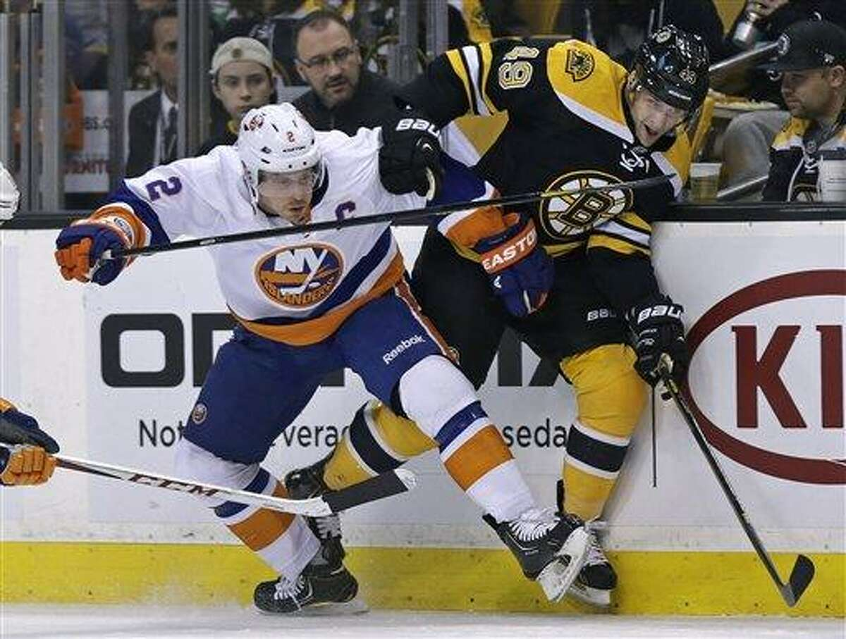 New York Islanders defenseman Mark Streit, of Switzerland, tangles with Boston Bruins center Rich Peverley, right, during the second period of an NHL hockey game in Boston, Friday, Jan. 25, 2013. (AP Photo/Charles Krupa)