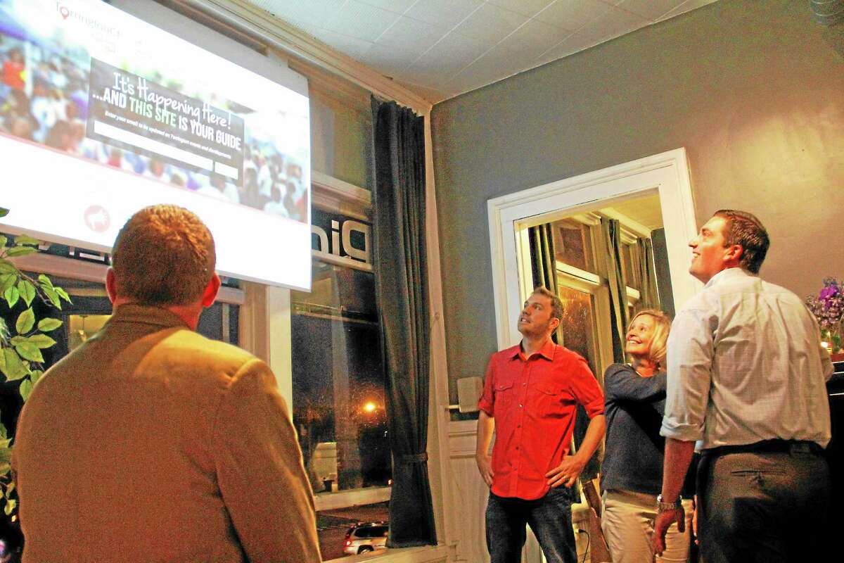 """From left: Evan Dobos (in red) owner of PictureThisWEBCENTER, Director of Economic Development Rose Ponte and Mayor Ryan Bingham react to the launching of the city's marketing website """"It's Happening Here"""" during a launch party on Friday, Sept. 27, in downtown Torrington."""