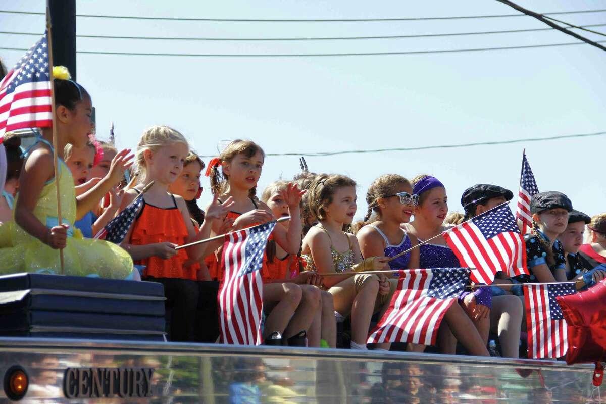 Children wave from atop a vehicle driven in Torrington's Memorial Day parade Monday. (Esteban L. Hernandez/Register Citizen)