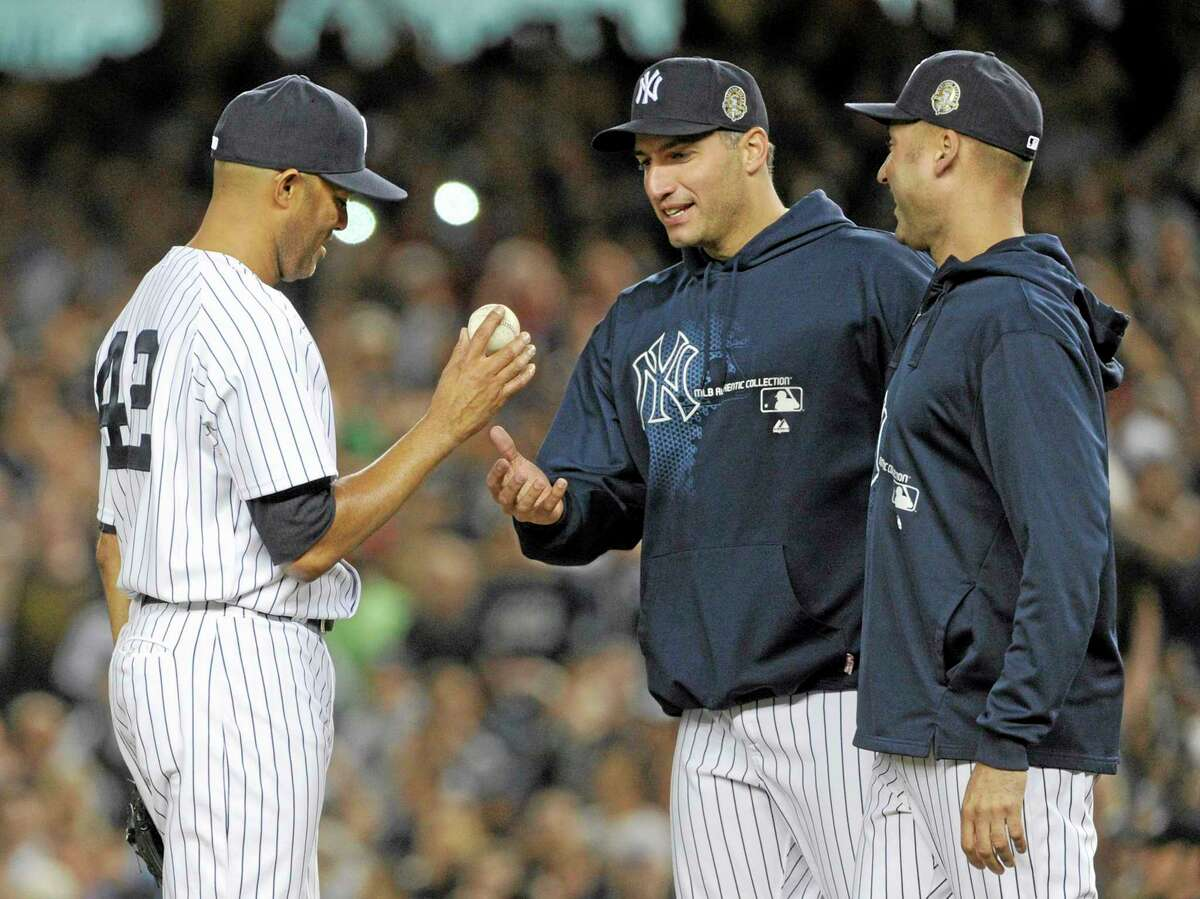 Mariano Rivera, left, hands the ball to Andy Pettitte as Derek Jeter, right, watches during the ninth inning of Thursday's game.