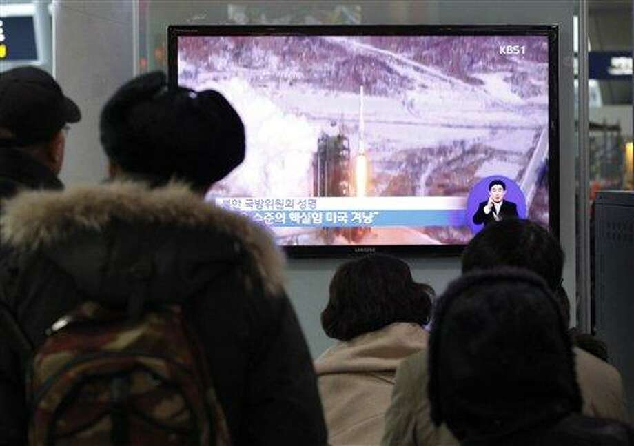People watch a TV news showing Dec. 12, 2012 file footage of the Unha rocket launch in North Korea, at Seoul Railway Station in Seoul, South Korea, Thursday, Jan. 24, 2013. North Korea's top governing body warned Thursday that the regime will conduct its third nuclear test in defiance of U.N. punishment, and made clear that its long-range rockets are designed to carry not only satellites but also warheads aimed at striking the United States. (AP Photo/Ahn Young-joon) Photo: AP / AP