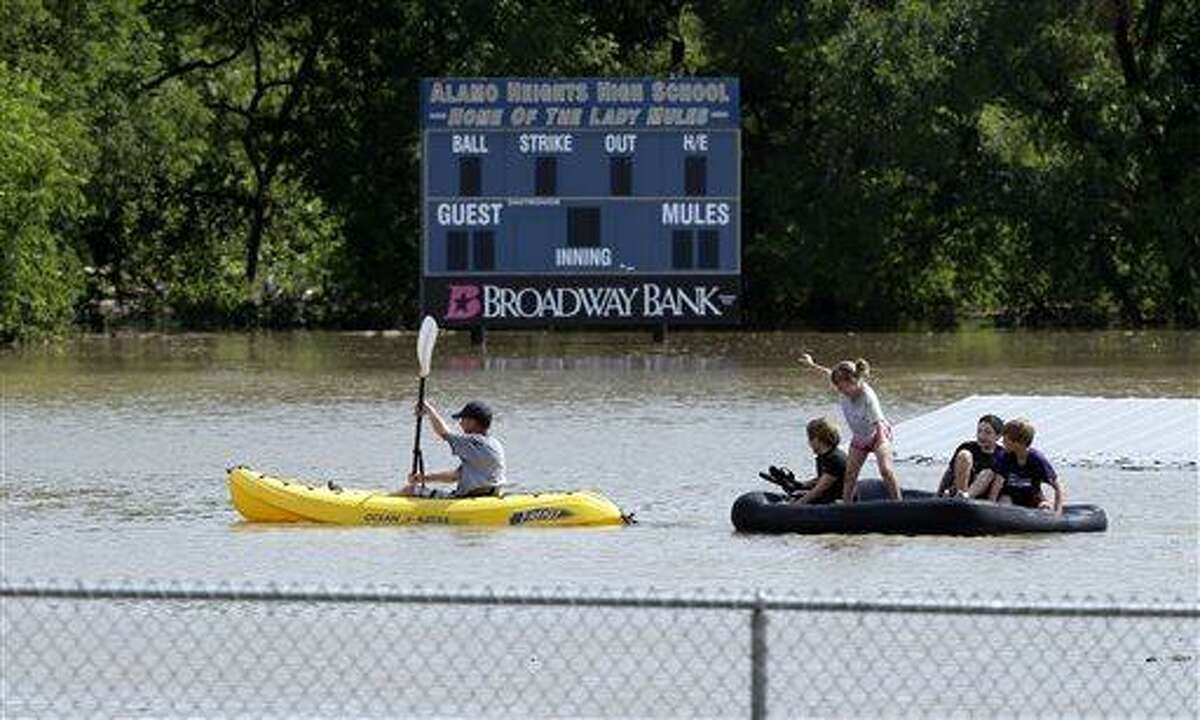 A kayaker pulls a raft with children around a flooded baseball park in San Antonio, Saturday, May 25, 2013, in San Antonio. San Antonio International Airport recorded more than nine inches of rain since midnight. (AP Photo/Eric Gay)