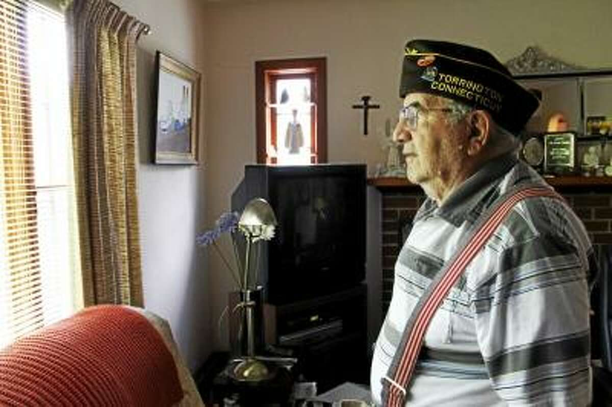 Frank Cimino looks out his living room window in Torrington on Saturday, May 23, 2013. A World War II veteran, Cimino is one of four Honorary Marshals for Torrington's 2013 Memorial Day Parade, which will take place on Monday at Coe Park starting at 9:30 a.m. He was nominated for the honor by a friends and received several awards and decorations for his service in the Pacific Theater in the War. (ESTEBAN L. HERNANDEZ/REGISTER CITIZEN)