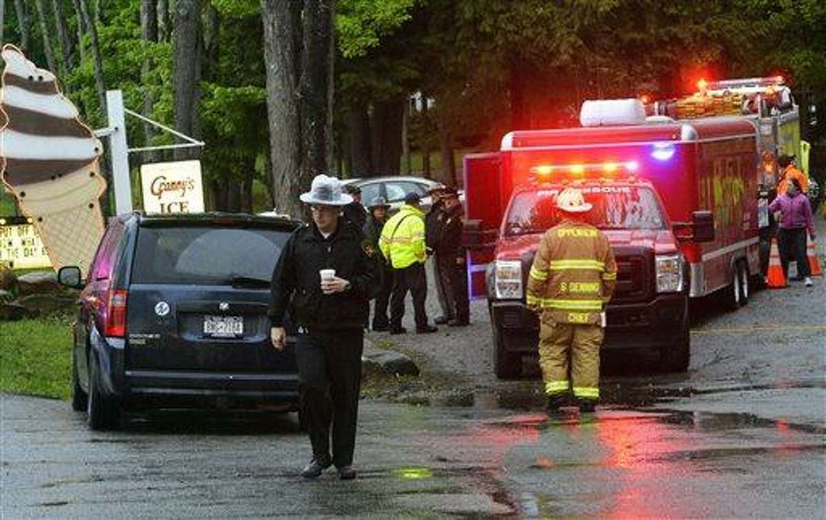 In this Friday, May 24, 2013 photo, rescue workers move about the staging area at Granny's Ice Cream across from the site of a plane crash in a wooded area off Route 10 in the town of Fulton in Ephratah, N.Y., after a small plane crashed killing two people. (AP Photo/The Daily Gazette, Peter R. Barber) TROY, SCHENECTADY; SARATOGA SPRINGS; ALBANY AND AMSTERDAM OUT