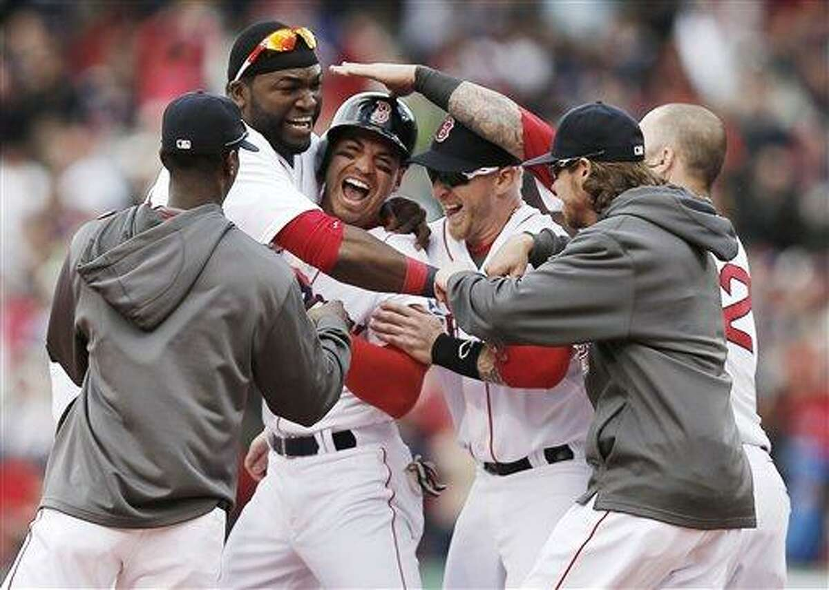Boston Red Sox's Jacoby Ellsbury, third from left, is mobbed by David Ortiz, second from left, and other teammates after his walk off two-run double during the ninth inning of Boston's 6-5 win over the Cleveland Indians in a baseball game at Fenway Park in Boston Sunday, May 26, 2013. (AP Photo/Winslow Townson)