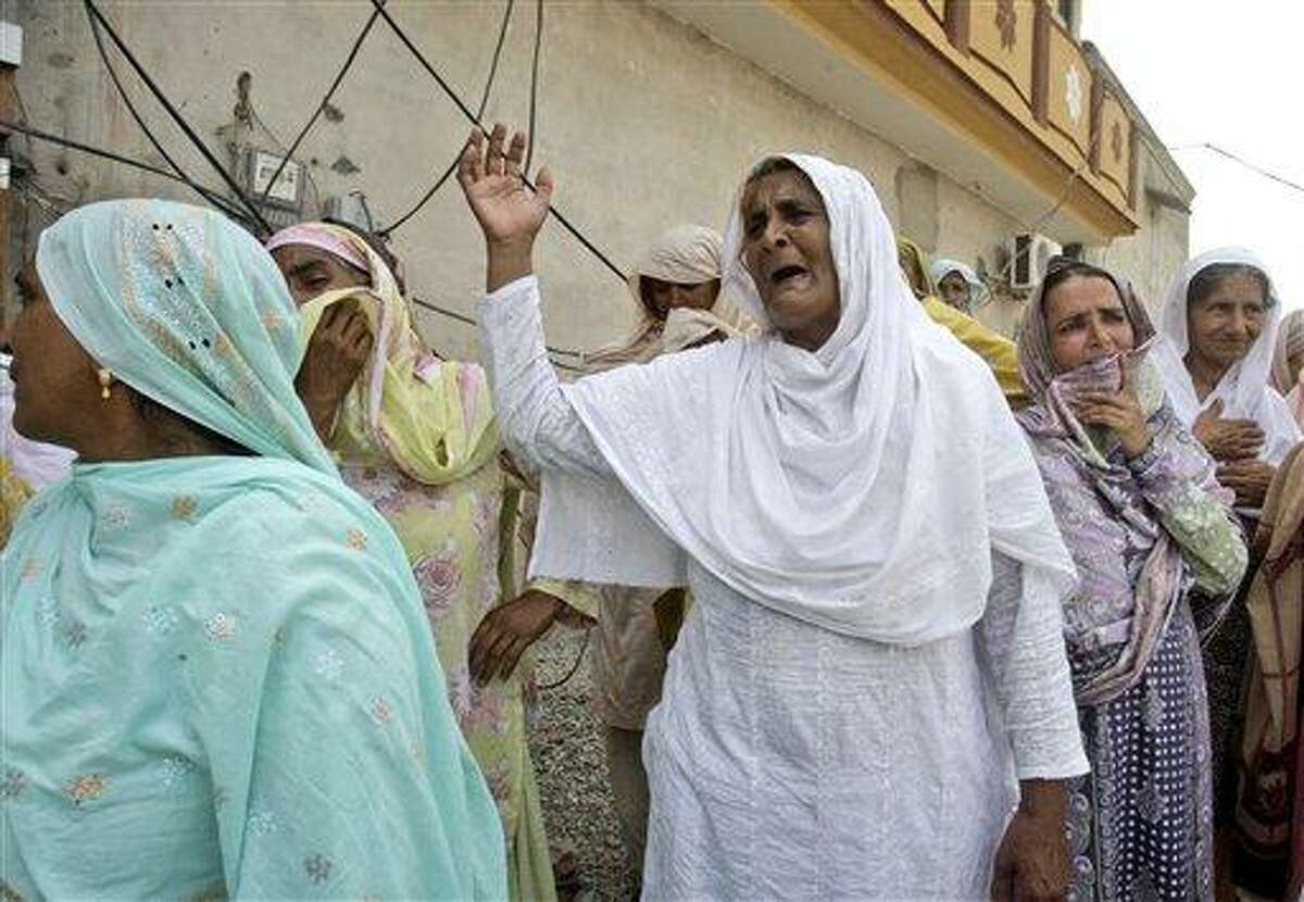 Pakistani women mourn the death of their relatives, who were killed in gas cylinder explosion on a minibus, in Gujrat, Pakistan, Saturday, May 25, 2013. Police say that a teacher was among more than a dozen people burned to death in eastern Pakistan when a minibus taking children to school suddenly caught fire. (AP Photo/K.M. Chaudary)