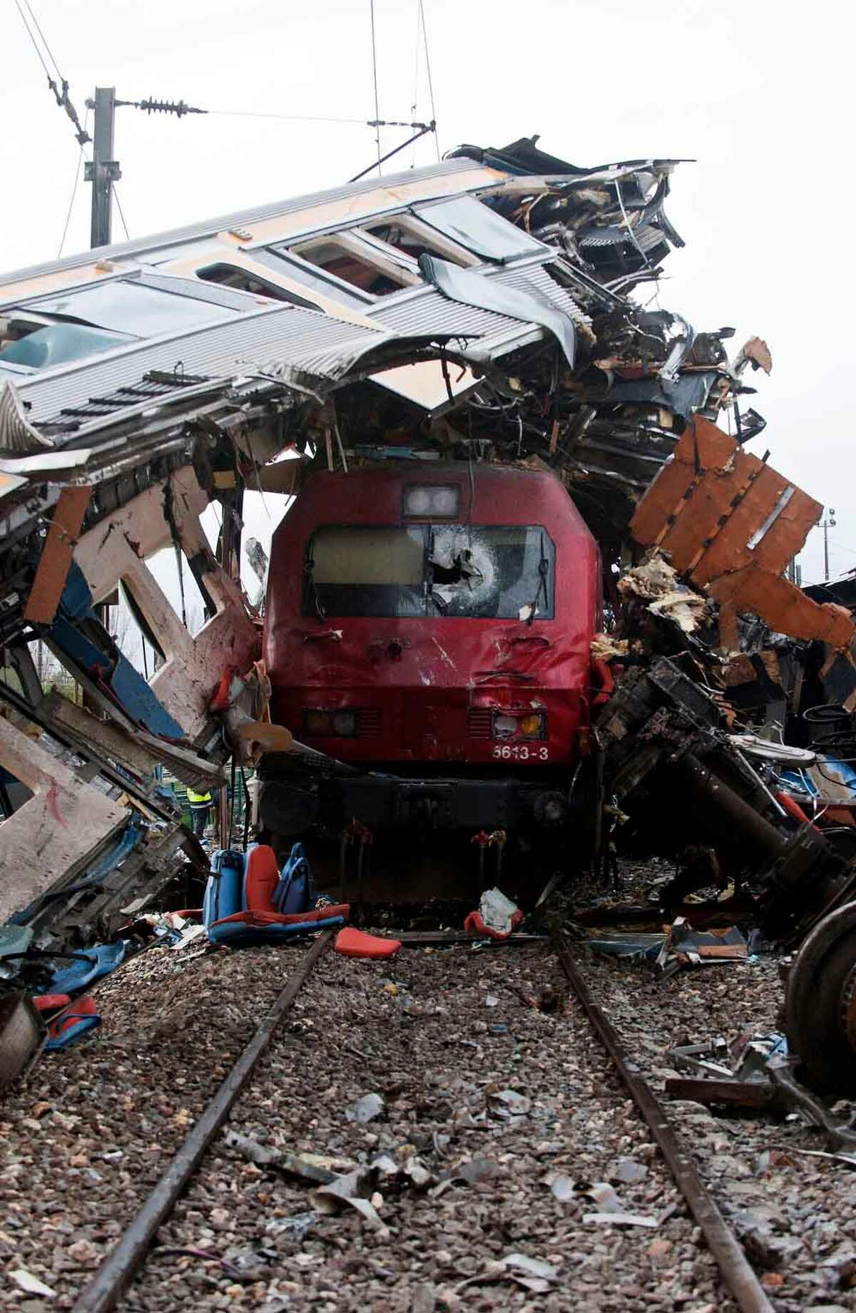 A train sits beneath the carriage of another train after a train crash at a station in Alfarelos, Portugal Tuesday Jan. 22, 2013. Emergency services say a high-speed intercity train rear-ended a local train waiting to enter a station in central Portugal, derailing several carriages leaving a pile of wreckage on Portugalís main north-south line, slightly injuring 21 people. Officials said the local train was waiting to pull into a station near Coimbra, 200 kilometers (120 miles) north of the capital, Lisbon, when the northbound intercity train slammed into it from behind at 9.15 p. m. (2100 GMT) on Monday. (AP Photo/Miguel Teixeira)