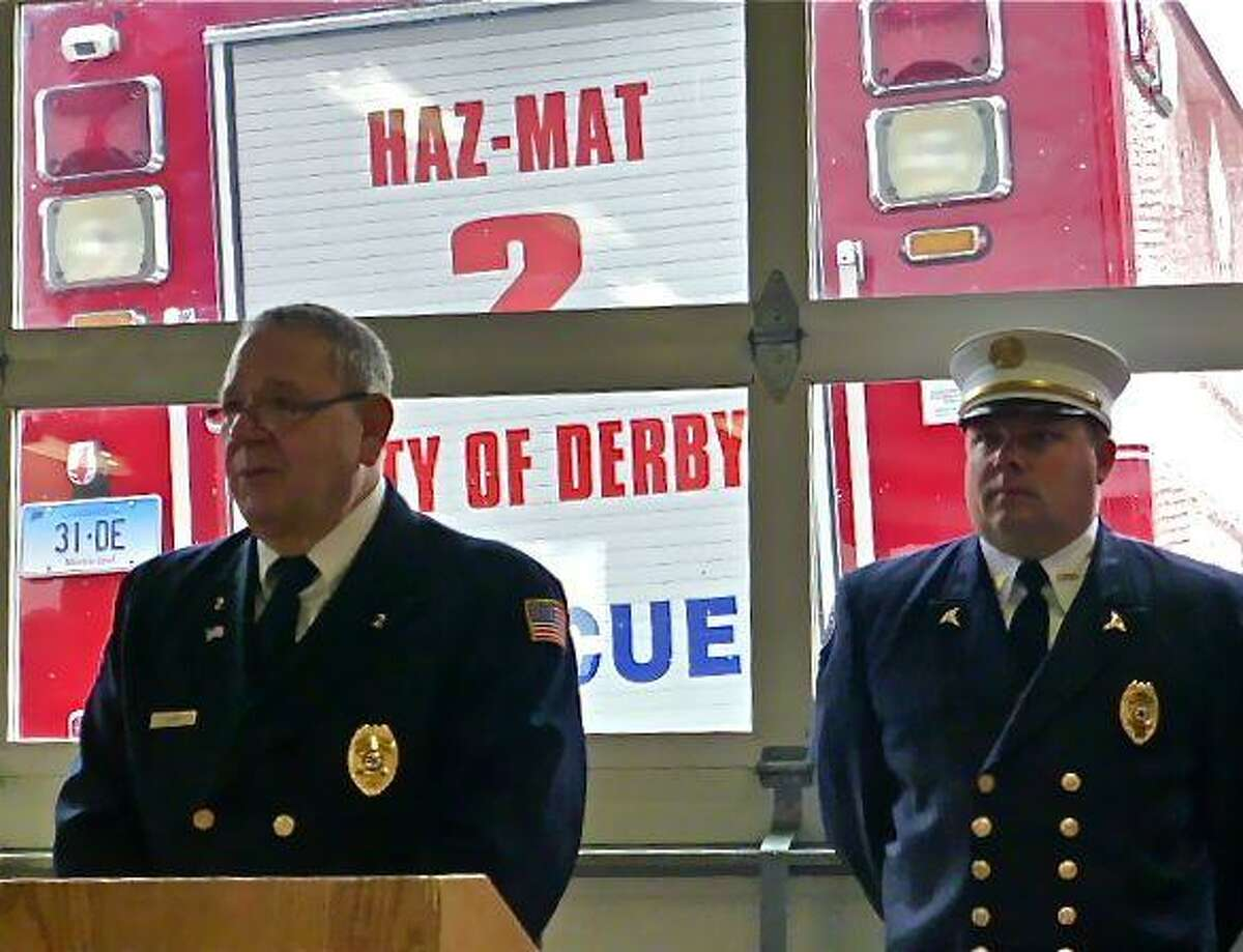 Derby resident Thomas Lenart Sr., left, son-in-law of the late Edward J. Cotter Jr., speaks Saturday in the Storm Engine Company firehouse during dedication of a park in Cotter's name at Derby's O'Sullivan's Island. Cotter was one of the founders of the former Fire Training School on the site. At right is Lenart's son, David Lenart. The ceremony was moved to the firehouse because of rain. Patricia Villers/Register