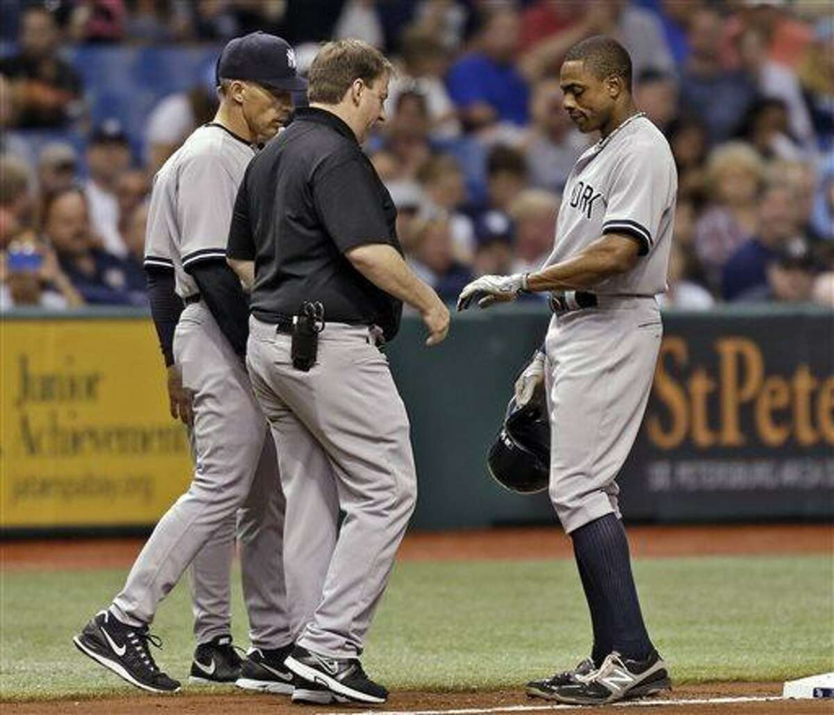 New York Yankees manager Joe Girardi, left, and a trainer look at Curtis Granderson's wrist during the fifth inning of a baseball game against the Tampa Bay Rays ,Friday, May 24, 2013, in St. Petersburg, Fla. (AP Photo/Chris O'Meara)